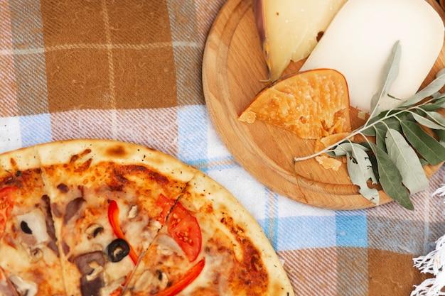 Pizza e prato de queijo em uma colcha xadrez. piquenique de verão