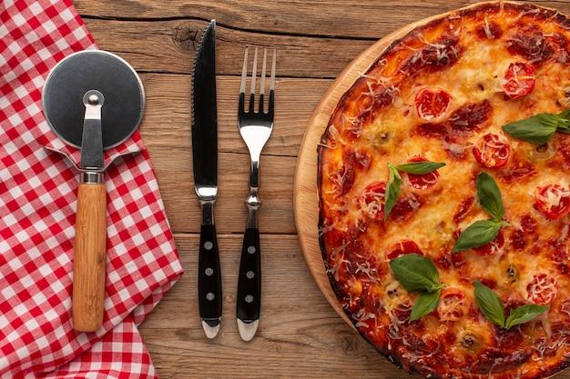Pizza e talheres deliciosos na horizontal