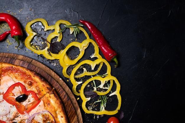 Pizza e vegetais em fundo escuro. conceito de espaço livre. cozinha italiana