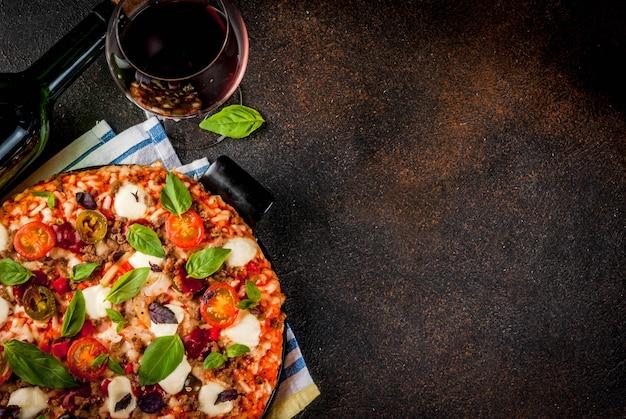 Pizza e vinho tinto em fundo escuro