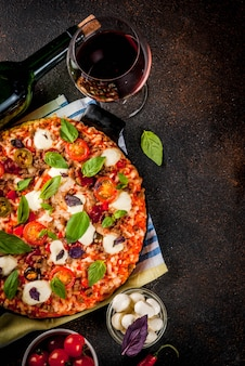 Pizza e vinho tinto na vista superior da superfície escura