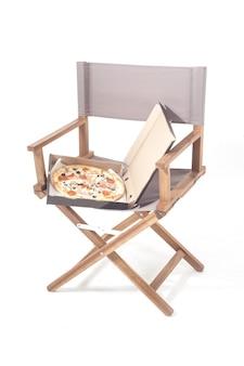 Pizza em caixa de pizza na cadeira do diretor isolada no fundo branco