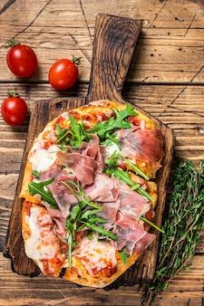 Pizza em fatias com presunto de parma, rúcula e queijo parmesão em uma tábua de madeira