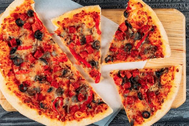 Pizza em fatias em um close de placa de pizza em um fundo escuro de estuque