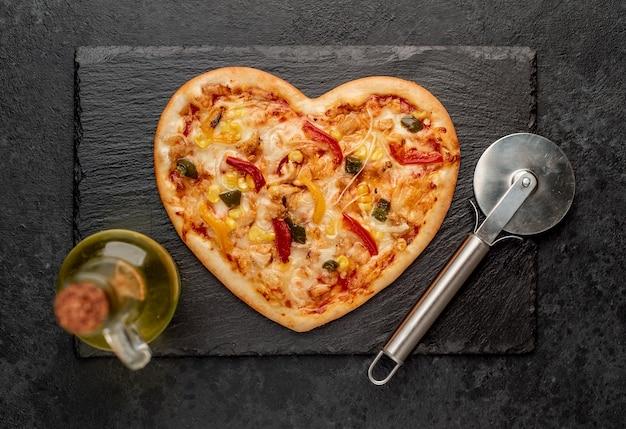 Pizza em forma de coração para o dia dos namorados em ardósia com cortador de pizza e azeite de oliva