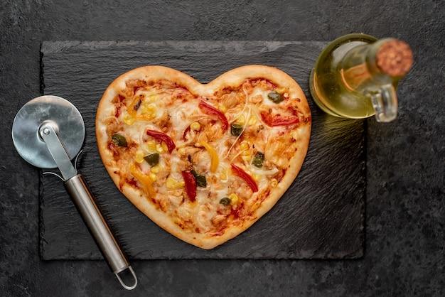 Pizza em forma de coração para o dia dos namorados em ardósia com cortador de pizza e azeite de oliva Foto Premium