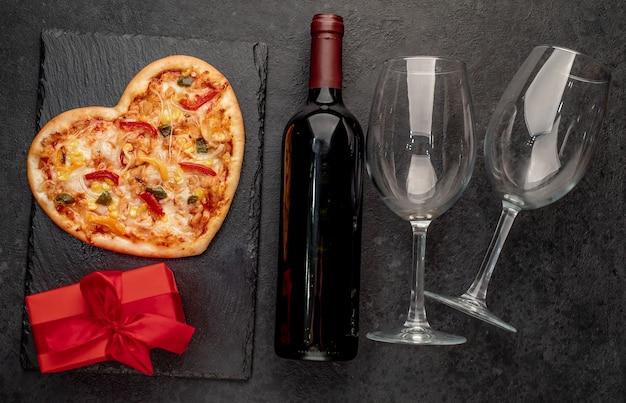 Pizza em formato de coração para o dia dos namorados com uma garrafa de vinho e dois copos em ardósia