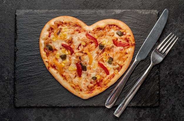 Pizza em formato de coração para o dia dos namorados em ardósia com talheres