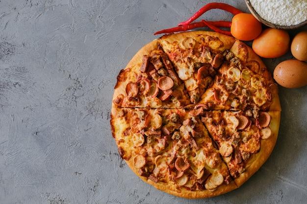 Pizza em fundo cinza rústico, vista superior. pizza com carne picada, aipo e queijo mussarela de perto.