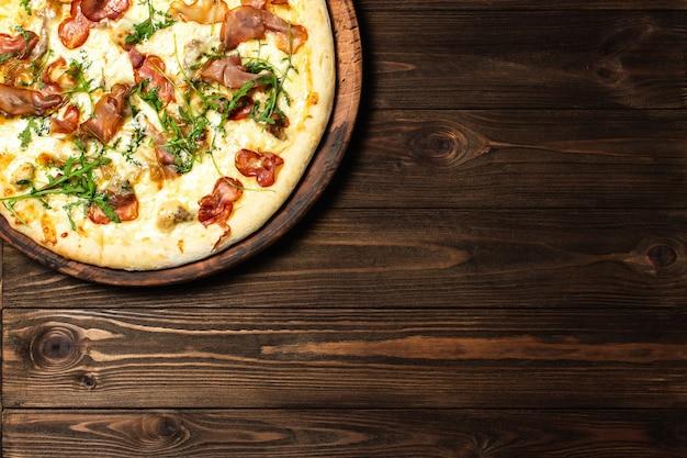 Pizza em fundo de mesa de madeira marrom escuro