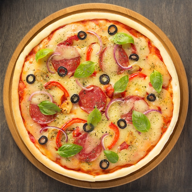 Pizza em mesa de madeira, vista de cima