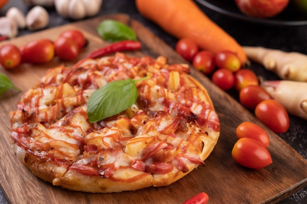 Pizza em uma bandeja de madeira com tomate pimenta e manjericão.