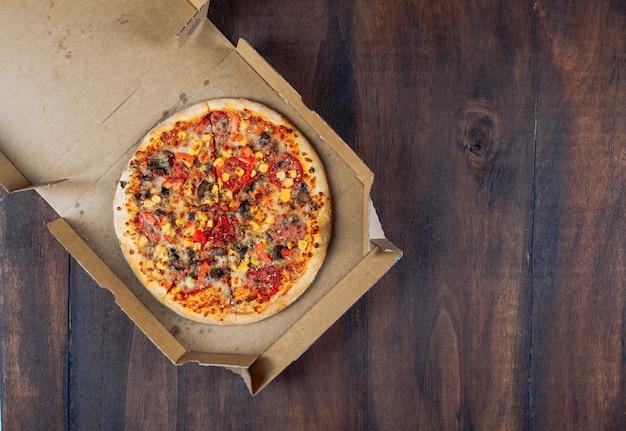 Pizza em uma caixa de pizza em um fundo escuro de madeira. configuração plana.