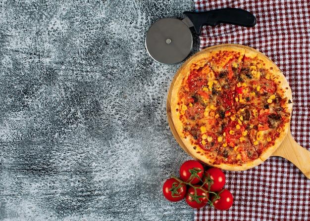 Pizza em uma tábua com tomates, vista superior do cortador de pizza em um fundo de pano de estuque e piquenique cinza