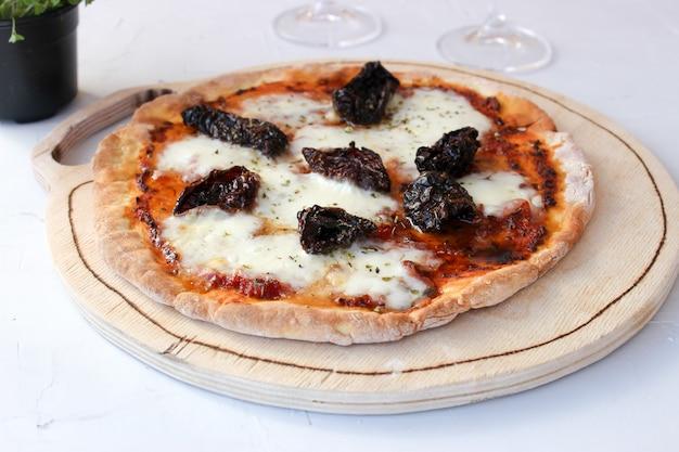 Pizza em uma tábua de madeira com mussarela, mini rúcula.