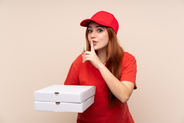 Pizza entrega adolescente menina segurando uma pizza fazendo o gesto de silêncio
