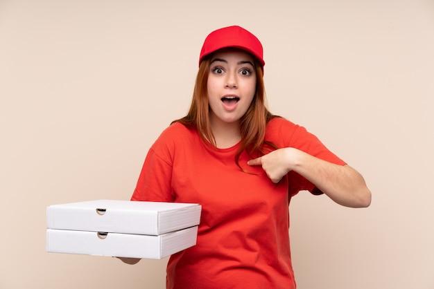 Pizza entrega adolescente mulher segurando uma pizza com expressão facial de surpresa