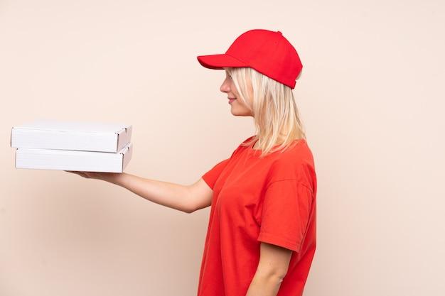 Pizza entrega mulher russa segurando uma pizza sobre parede isolada com expressão feliz