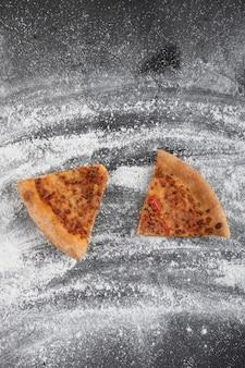 Pizza fatiada caseira na superfície preta com farinha de trigo derramada
