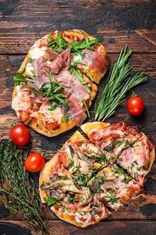Pizza fatiada com presunto de parma presunto, rúcula e queijo parmesão. fundo de madeira escuro. vista do topo.