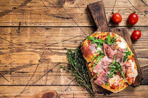 Pizza fatiada com presunto de parma, rúcula e queijo parmesão em uma placa de madeira. fundo de madeira. vista do topo. copie o espaço.