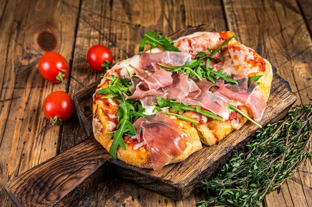 Pizza fatiada com presunto de parma, rúcula e queijo parmesão em uma placa de madeira. fundo de madeira. vista do topo.