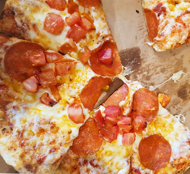 Pizza fatiada deitada em uma caixa de papelão, vista de cima