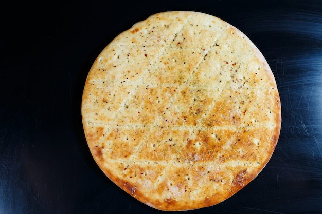 Pizza fatiada em um fundo de pedra preta, vista superior. focaccia recém-assada com queijo