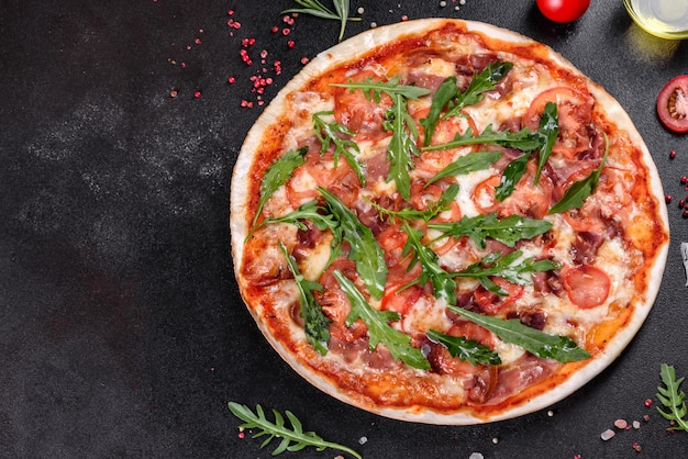 Pizza fresca assada no forno com rúcula, salame, tomate cereja e mussarela. cozinha italiana
