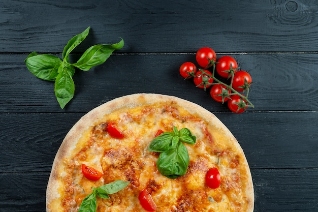 Pizza fresca caseiro margherita com molho vermelho, manjericão e tomate cereja em um preto de madeira com espaço de cópia.