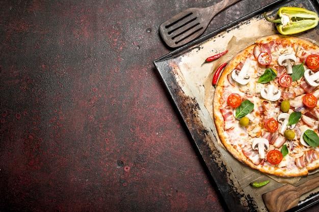 Pizza fresca com cogumelos, bacon e tomate. .