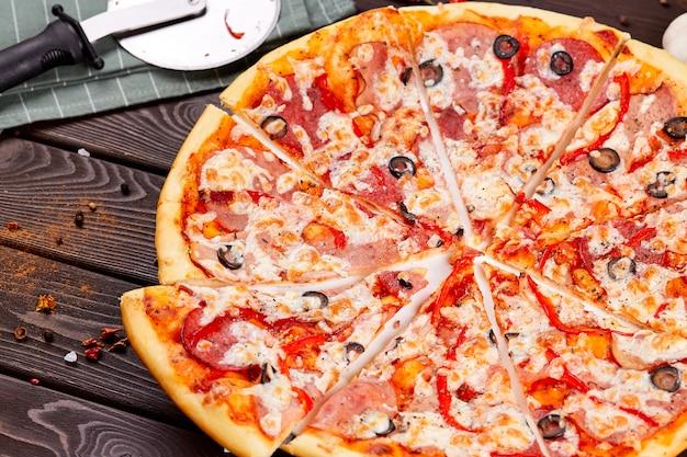 Pizza fresca com tomate, queijo e cogumelos na mesa de madeira closeup.