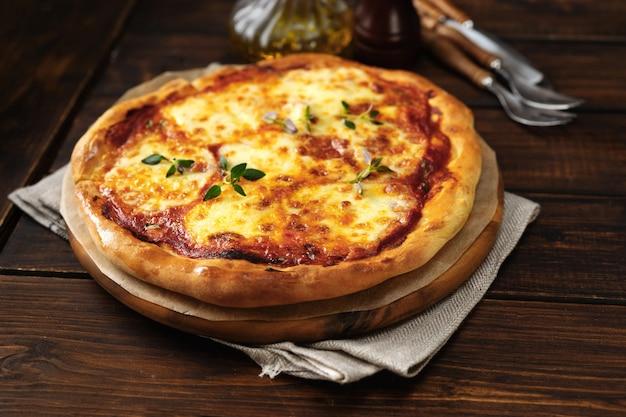 Pizza fresca e apetitosa margherita no fundo escuro de madeira