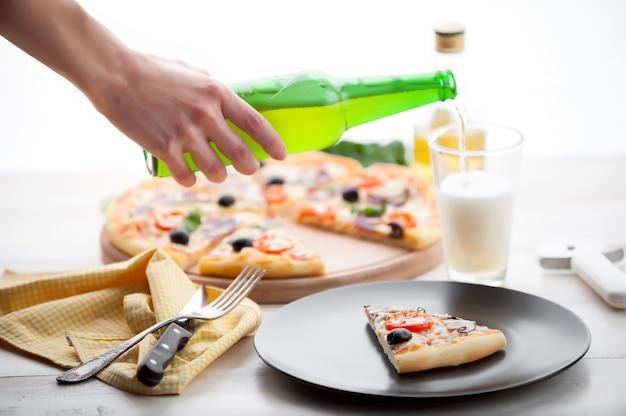 Pizza fresca em estilo italiano rústico com cogumelos de azeitonas espasmódicas e três tipos de queijo em um fundo claro de madeira com uma garrafa de cerveja gelada