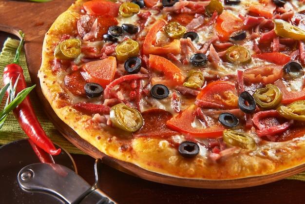Pizza fresca na mesa de madeira com ingredientes