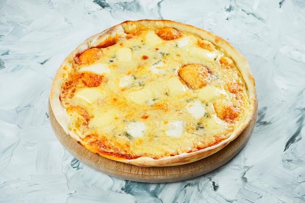 Pizza grande com 4 queijos assada no forno com mussarela e queijo azul com mofo em uma placa de madeira. cozinha italiana