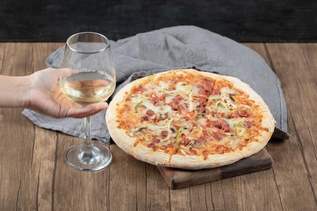 Pizza grande com margarita e uma taça de vinho branco por perto