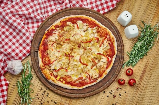 Pizza havaiana com queijo derretido, abacaxi, frango, milho na bandeja de madeira. pizza em composição com ingredientes na mesa de madeira.