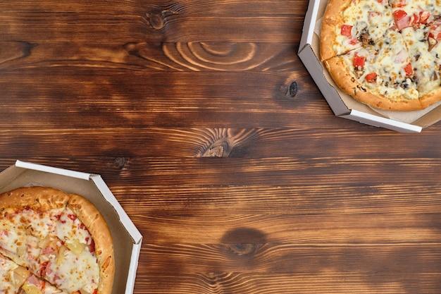 Pizza havaiana e carbonara em embalagens de papelão com vista superior e cópia espaço