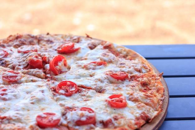 Pizza inteira margarita com tomates e queijo.