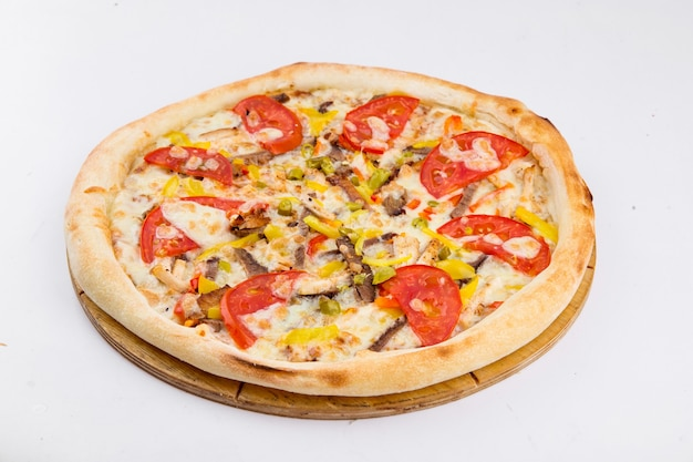 Pizza isolada com carne e tomate em uma placa de madeira