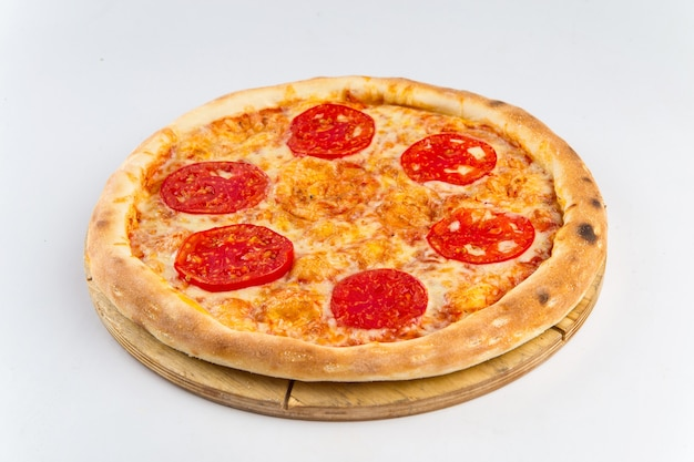 Pizza isolada com tomate em uma placa de madeira