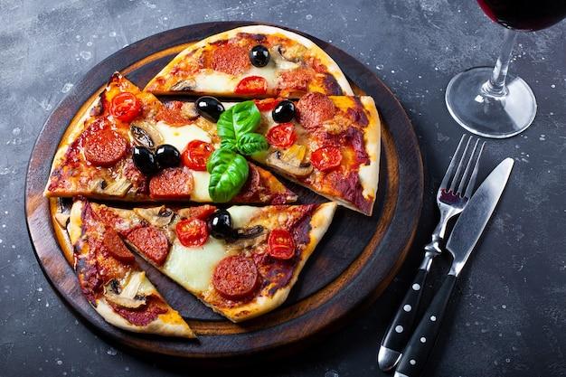 Pizza italiana caseira com mussarela, linguiça calabresa, azeitonas e manjericão e um copo de vinho tinto na mesa.