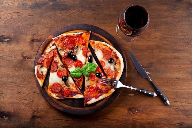 Pizza italiana caseira com mussarela, linguiça calabresa, azeitonas e manjericão e um copo de vinho tinto na vista de cima da mesa.