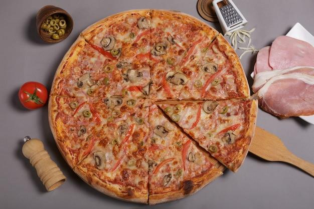 Pizza italiana com azeitonas verdes e presunto feito em casa. ingredientes em torno da pizza.