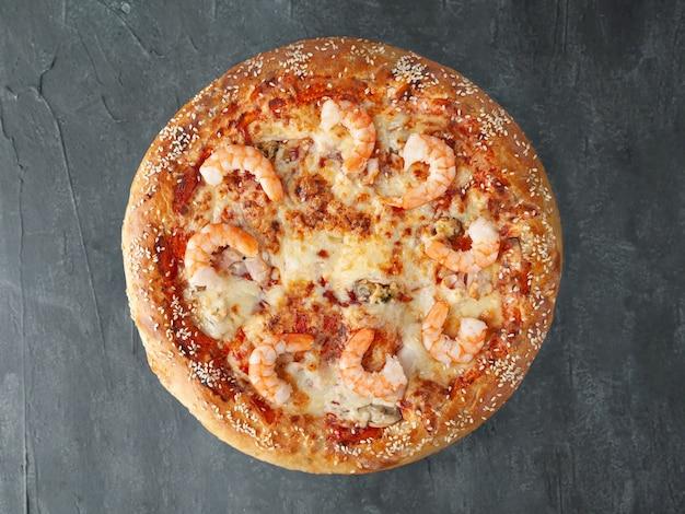 Pizza italiana. com camarão tigre, lula, mexilhão, molho de tomate, queijo mussarela. lado largo. vista de cima. sobre um fundo cinza de concreto. isolado.