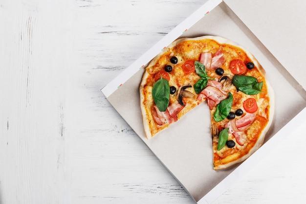 Pizza italiana com cogumelos, manjericão, tomate, azeitonas e queijo na caixa de entrega