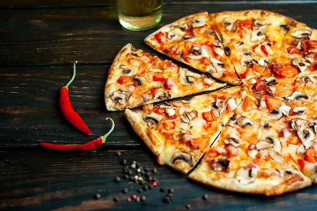 Pizza italiana com cogumelos, tomate e queijo na madeira