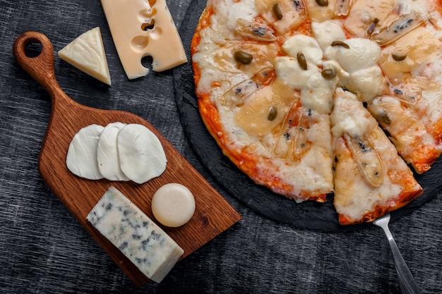 Pizza italiana com diferentes tipos de queijo em uma pedra e um quadro preto riscado.