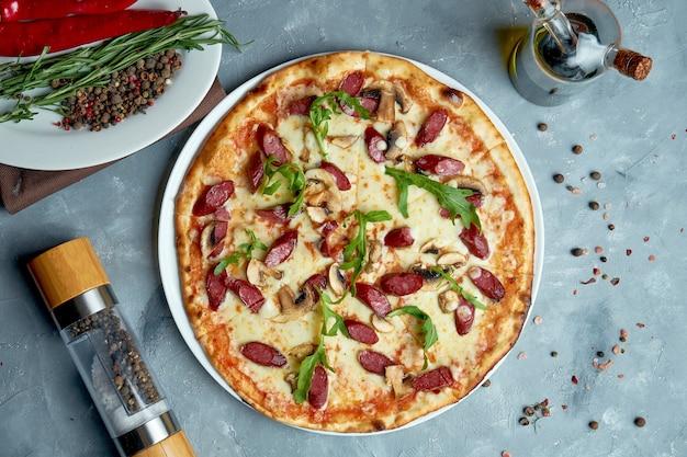 Pizza italiana com linguiça defumada, cogumelos, rúcula. vista de cima, comida plana leigos.